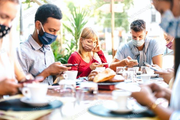 Freunde nutzen Mobiltelefone an der Kaffeebar