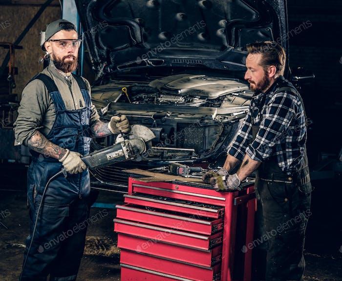Zwei bärtige Mechanik mit einem Winkelschleifer.