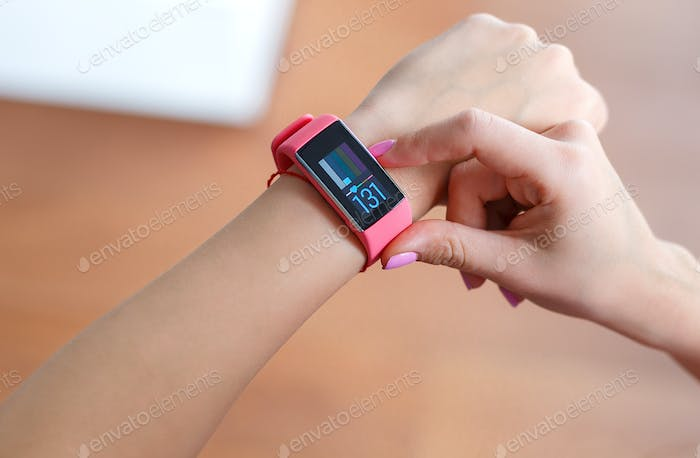 Isolated female hand with pink smartwatch taking pulse after exercising