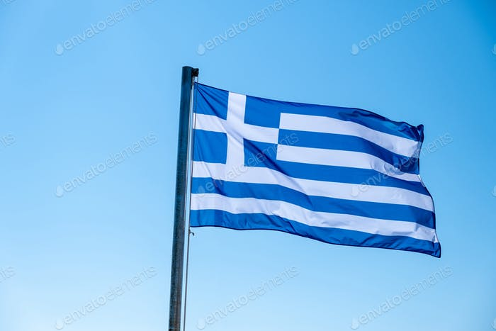 Greek flag waving against blue sky background.