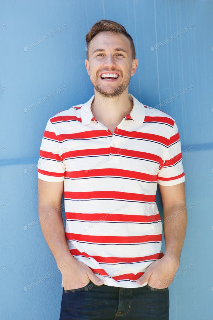 handsome young man in striped shirt laughing against blue wall