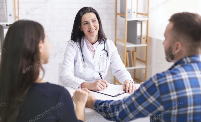 Professional doctor consulting young married couple at office