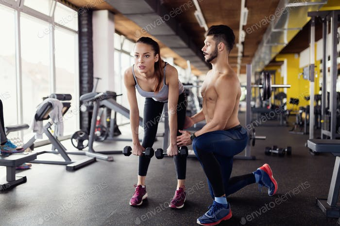Young attractive woman doing exercises in gym