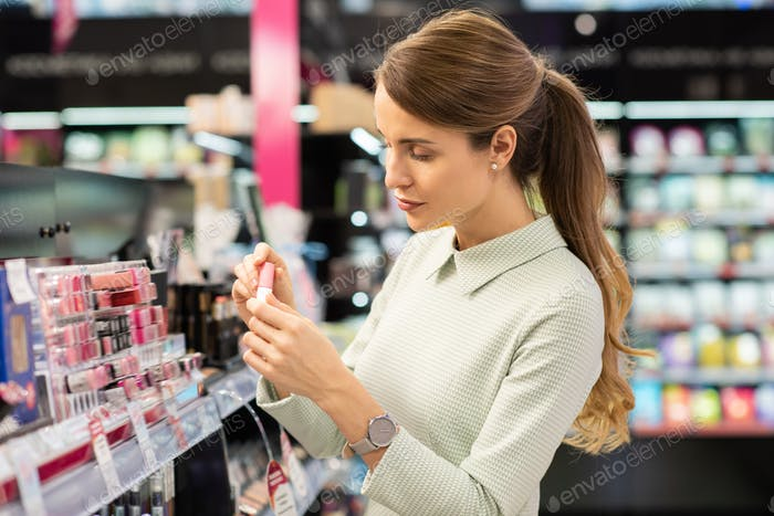 Pretty young woman in smart dress holding lip gloss and going to test it on hand