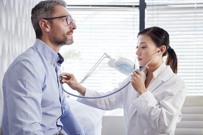 Reifen männlich Patient mit medizinische Prüfung mit Frau Arzt in office