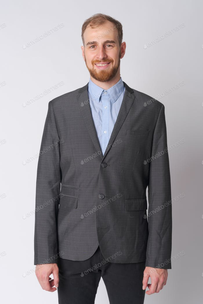 Portrait of happy young bearded businessman smiling