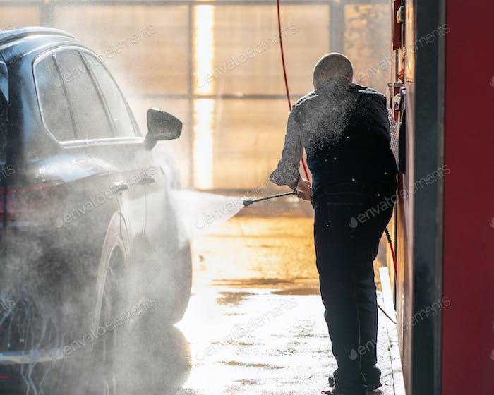 Mann wäscht Auto in der Autowäsche, gießt Wasser aus dem Schlauch. Sonnenlicht und Wasserspritzer in der Kontur
