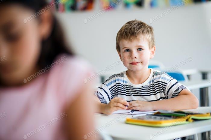 Ein kleiner Schuljunge sitzt am Schreibtisch im Klassenzimmer, Blick auf die Kamera