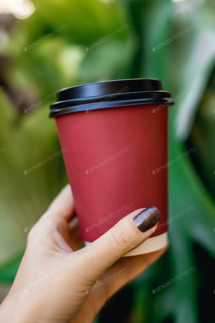 Woman's hand holding red cup of coffee on green natural background