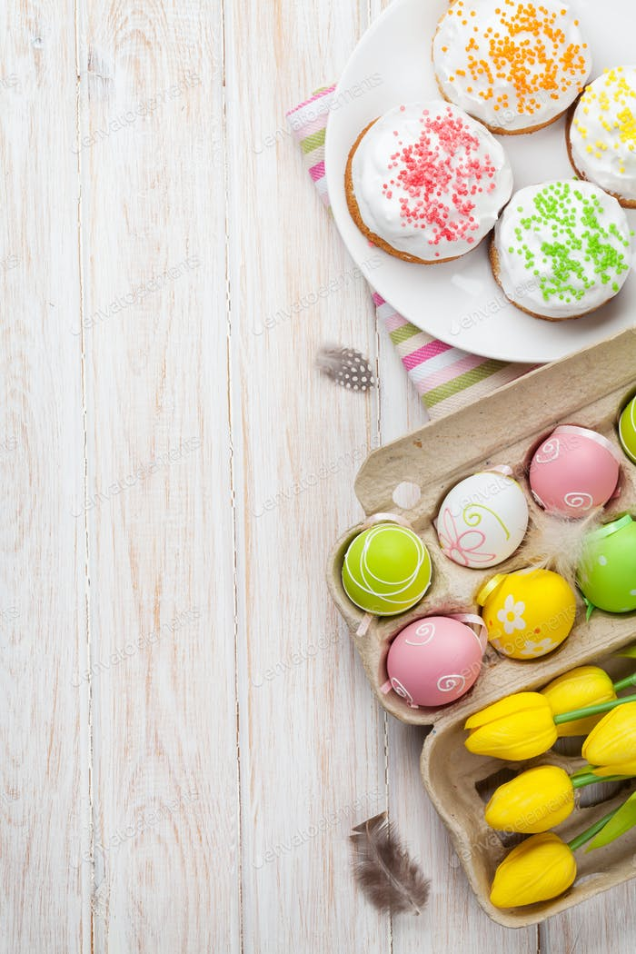 Easter with yellow tulips, colorful eggs and traditional cakes