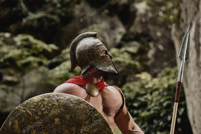 Gladiator in helmet posing with arms
