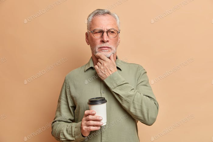 Pensive wrinkled man stands in thoughtful pose rubs chin and tries to make his mind contemplates abo
