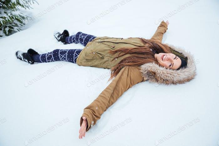 Fröhlich hübsche Frau liegend auf Schnee im Winter