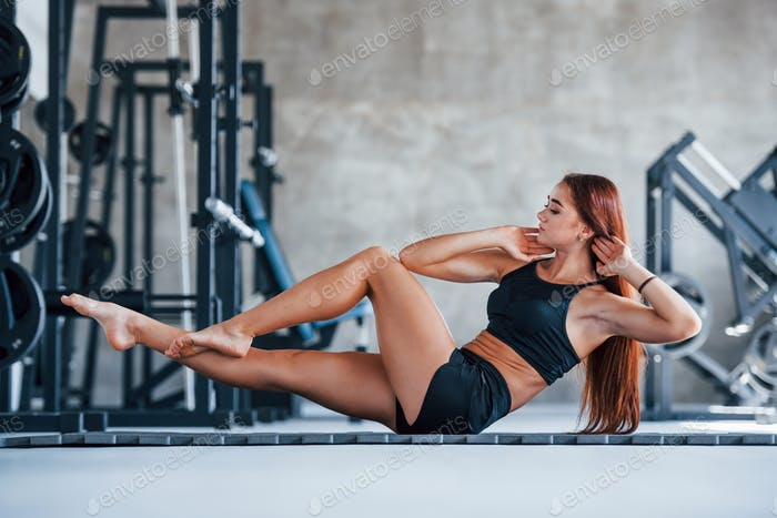 Young fitness girl in black sportive clothes doing yoga exercises in gym