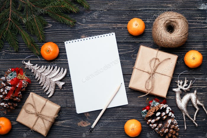 Christmas time concept. Gifts, presents and wish list or letter on dark wooden background