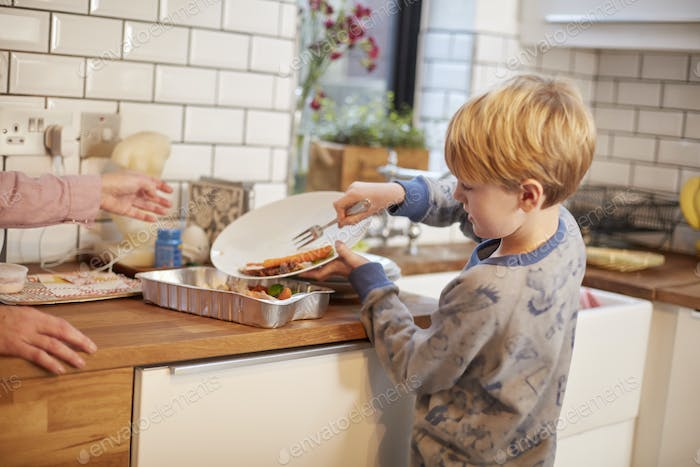 A boy clearing a plate after a meal.