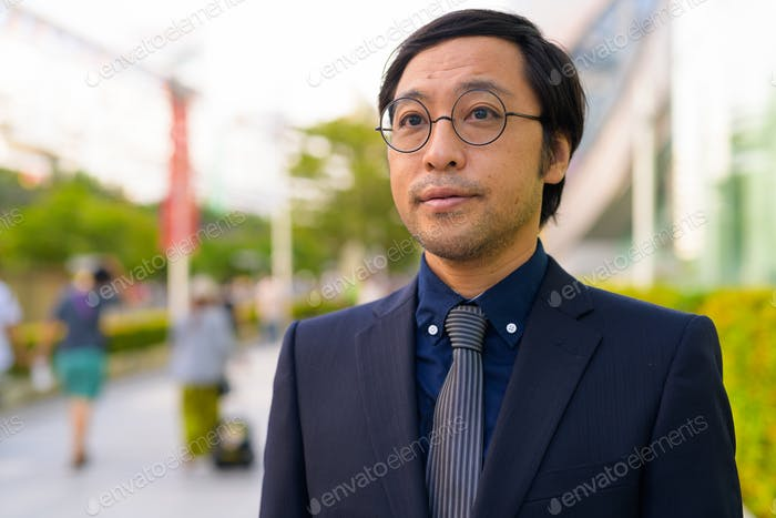 Face of Asian businessman thinking with nature in the city outdoors