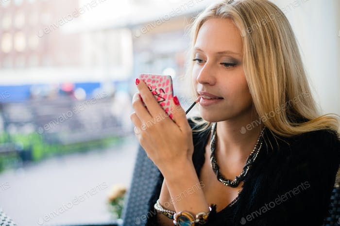 Side portrait of a smart young woman using mirror to apply lipstick cosmetics while visiting city
