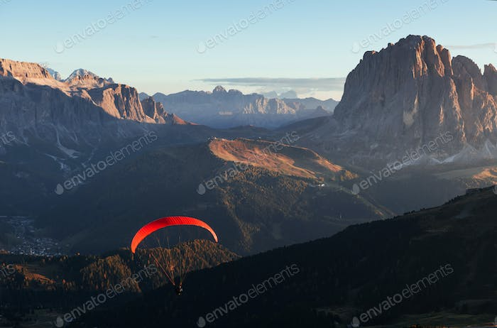 Paraglider with red parachute flies over the mountains filled with trees in the sunlight