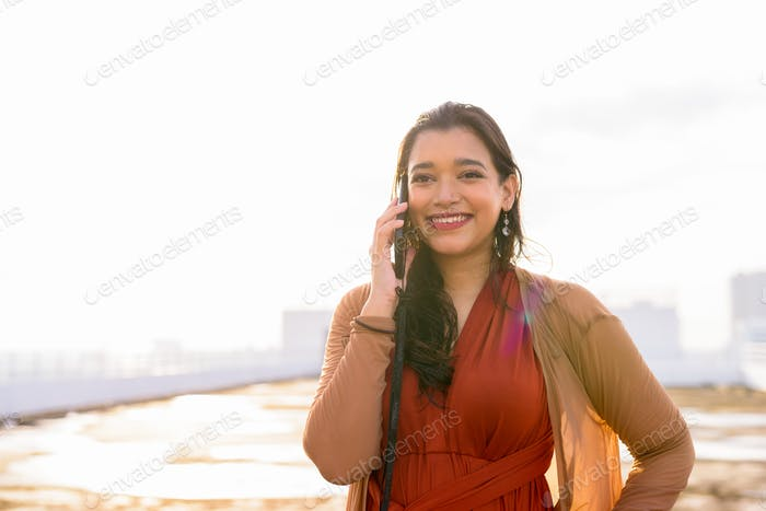 Happy young beautiful Indian woman talking on the phone at rooftop of the building