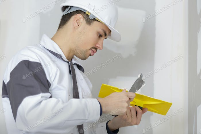 builder plastering cement on a wall