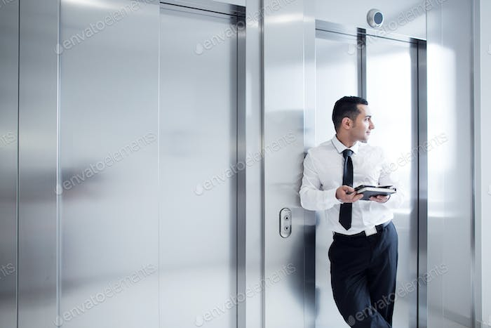 Business man leaning on elevator