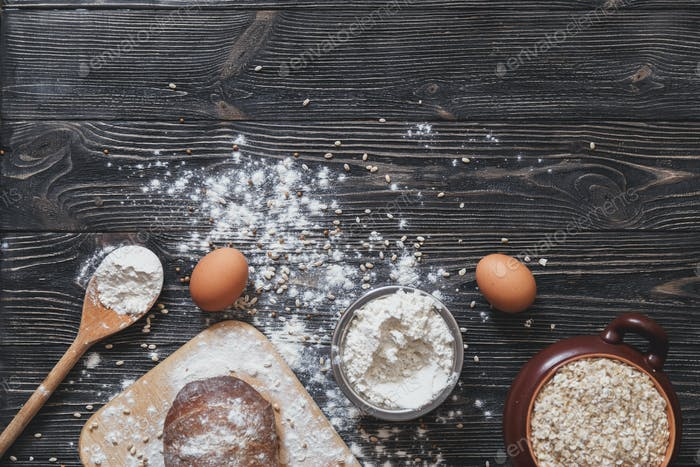 Baking bread at home on a rustic wooden table with space for text layout. View from above.