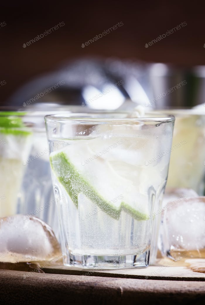 Cocktail with pomelo and ice, dark wood background, selective focus