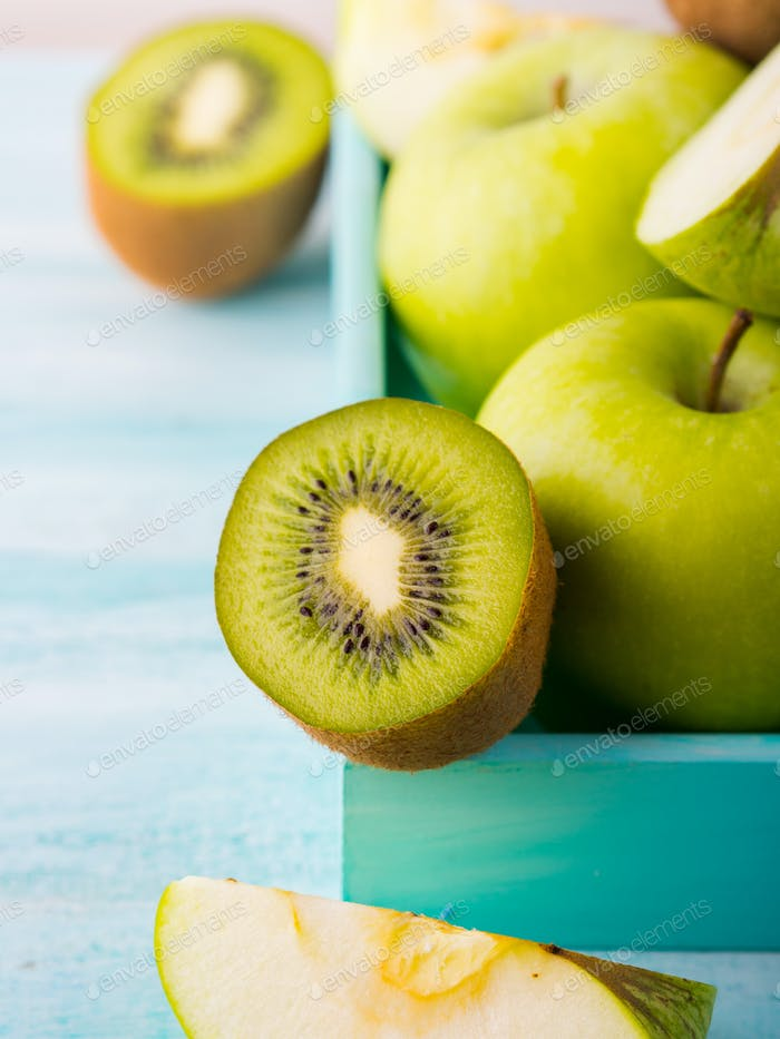 Green apples and kiwi on turquoise