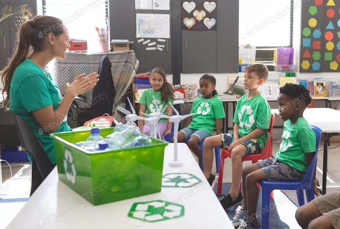teacher interacting with school kids about green energy and recycle at desk in classroom at school