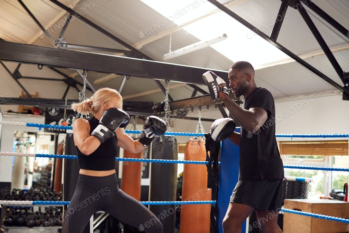 Männliche Personal Trainer Sparring Mit Weiblichen Boxer In Gym Mit Trainingshandschuhe