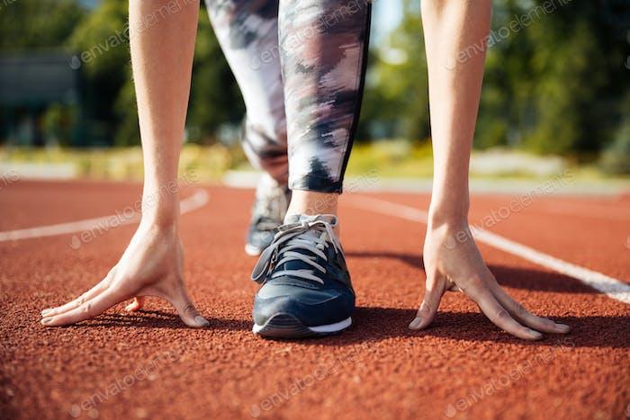 Ausgeschnittenes Bild einer weiblichen Sprinter, die bereit ist zu laufen