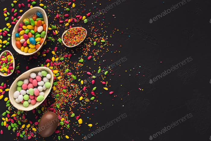 Chocolate eggs and colorful candies with copy space