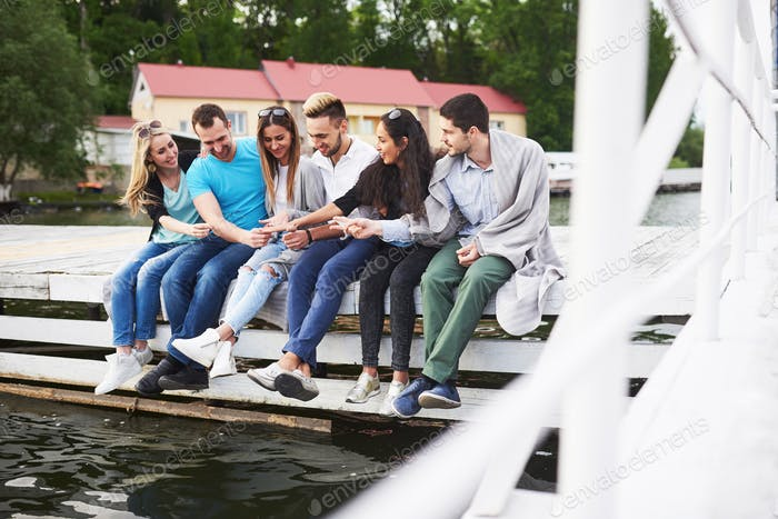 Portrait of happy young friends sitting on a pier at the lake