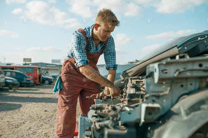 Male mechanic unscrew engine on car junkyard