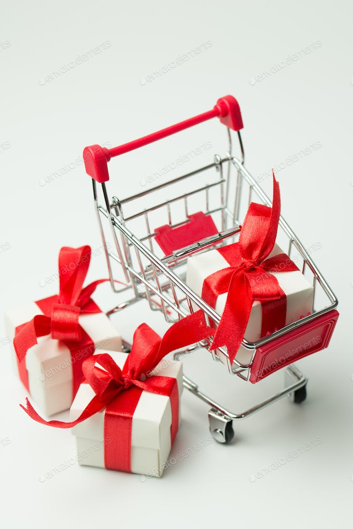 White gift box tied with red ribbon in a shopping cart