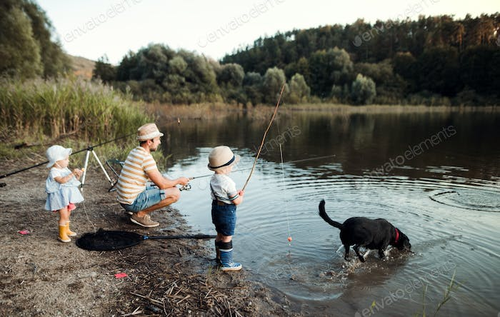 A mature father with small toddler children and a dog fishing by a lake.