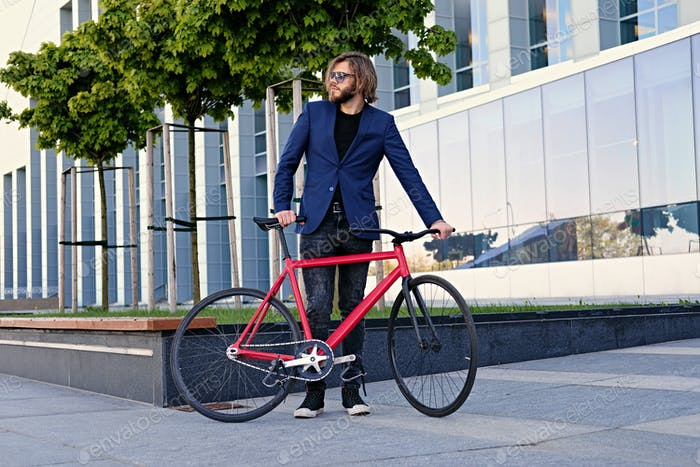 A man with single speed bicycle in a city park.