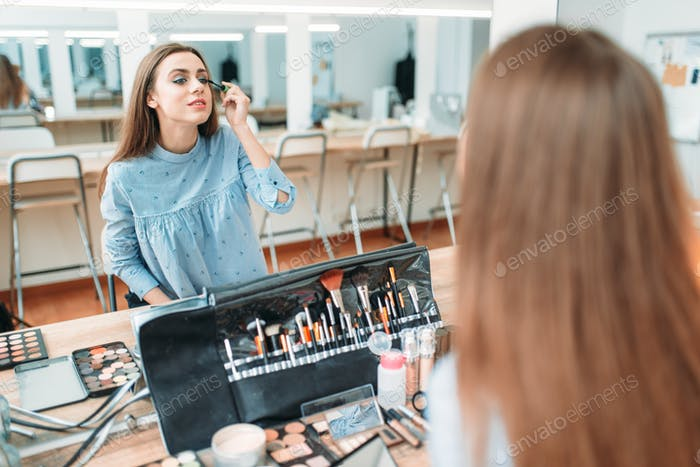 Woman work with own face in beauty studio