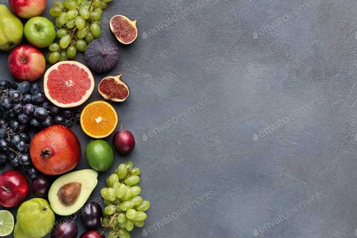 Fresh fruits border on gray background top view