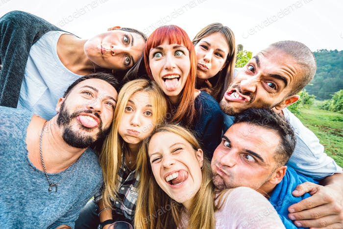 Best friends taking funny selfie at picnic excursion sticking out tongue