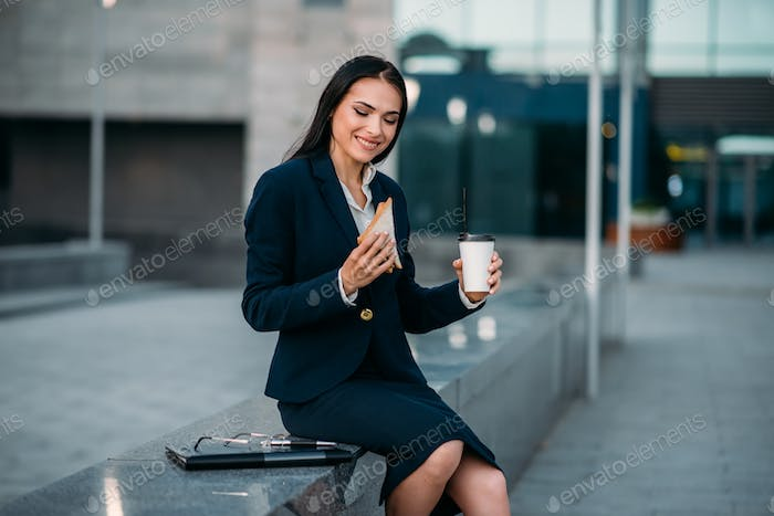 Happy business woman with sandwich and coffee