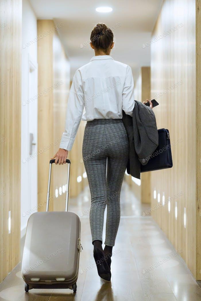 Mujer de negocios joven de moda caminando con maleta buscando fo