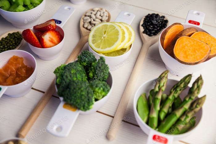 Portion cups and spoons of healthy ingredients on wooden table