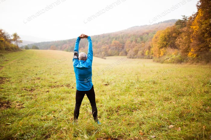 Senior runner with smartphone doing stretching. Autumn nature.
