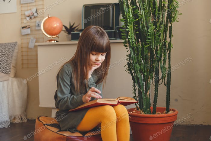 charmante kleine Mädchen lesen Buch in Ihr Zimmer