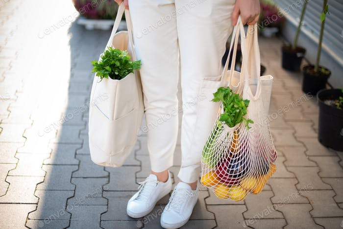 Girl holding mesh shopping bag and cotton shopper with vegetables without plastic bags at farmers
