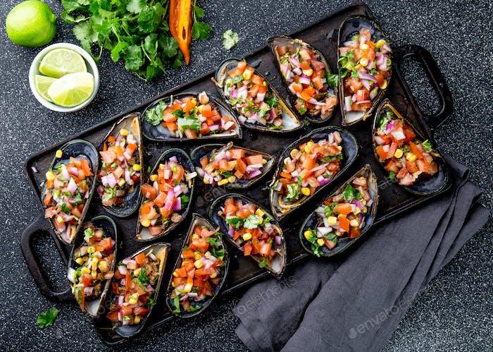 Big mussels, choros zapatos seasoned with purple onion, tomatoes, corn and lemon