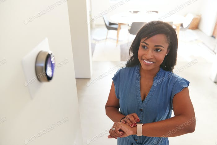 Woman Adjusting Digital Central Heating Thermostat Using Smart Watch At Home