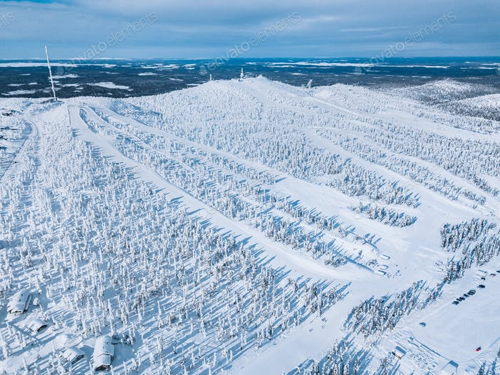 Aerial view of snow covered forest and ski resort slope in winter Finland Lapland.